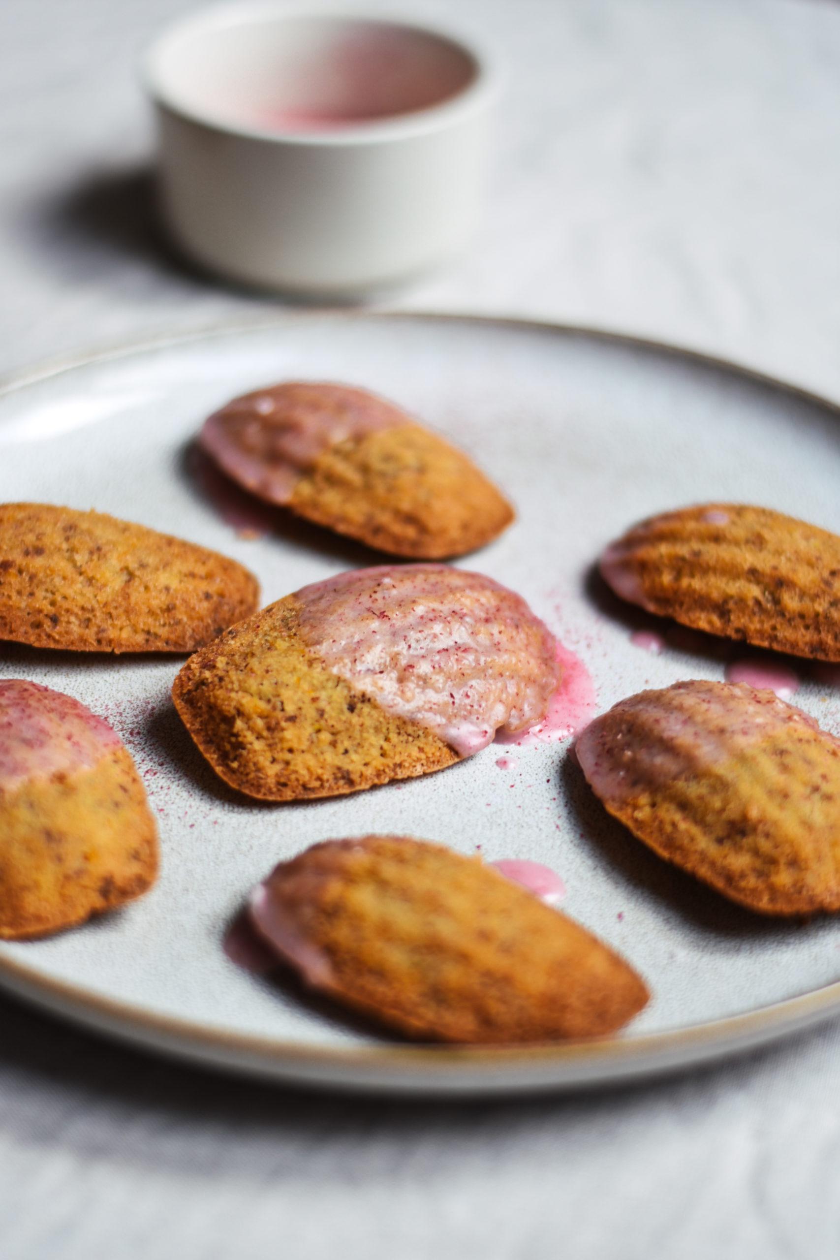 Vegane, glutenfreie Madeleines auf einem Teller mit Grapefruitfrosting im Hintergrund